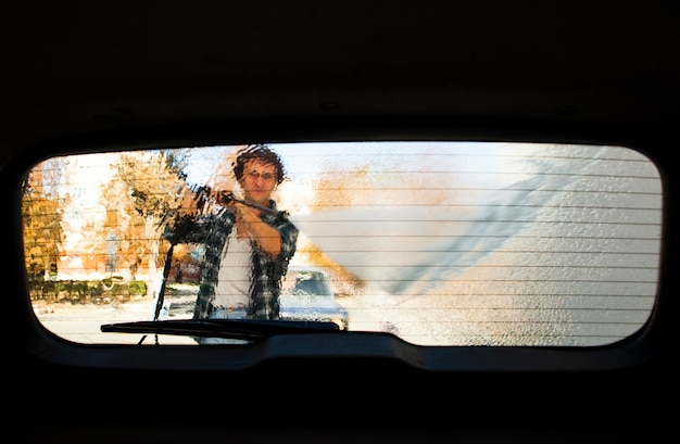 Mannschattenbildansicht, die ein autofenster wäscht