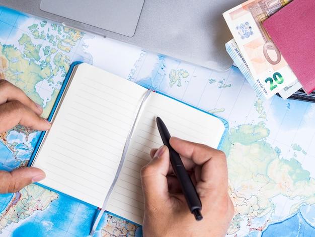 Mannschreiben in einem notizbuch nahe bei einer geldbörse