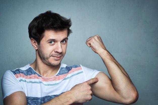 Mannshow auf seinem muskelbizeps nach dem eignungstraining