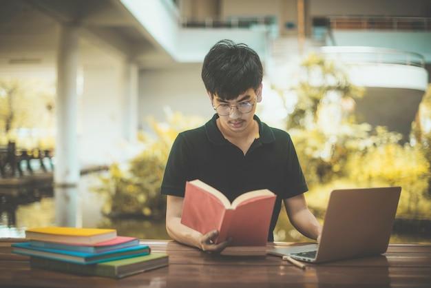 Mannstudent mit gläsern lesebüchern in der bibliothek