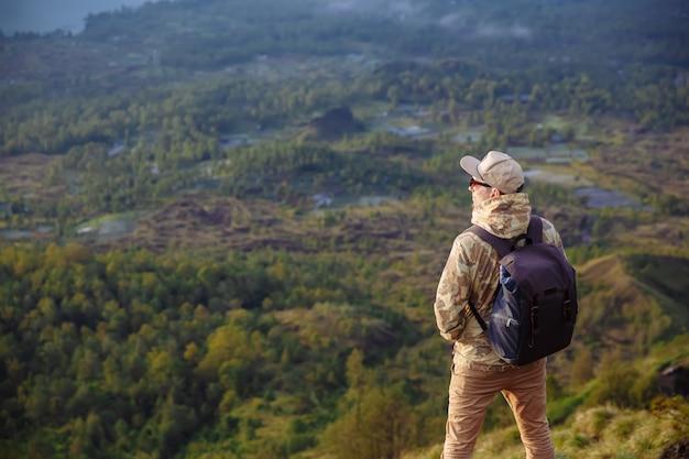 Manntourist betrachtet den sonnenaufgang auf dem vulkan batur auf der insel von blai in indonesien. wanderermann mit rucksackreise auf spitzenvulkan, reisekonzept