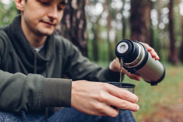 Manntourist gießt heißen tee aus thermosflasche im herbstwald heraus