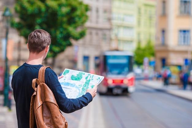 Manntourist mit einem stadtplan, der den zug in der europäischen stadt wartet.