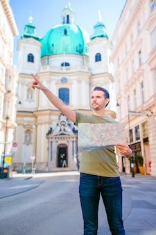 Manntourist mit einem stadtplan in europa-straße. kaukasischer junge, der mit karte der europäischen stadt schaut.