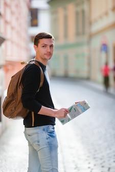 Manntourist mit einem stadtplan und einem rucksack in europa-straße. kaukasischer junge, der mit karte der europäischen stadt auf der suche nach anziehungskräften schaut.
