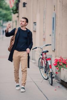 Manntourist mit einem stadtplan und einem rucksack in europa-straße. kaukasischer junge, der mit karte der europäischen stadt schaut.