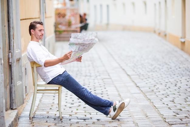 Manntourist mit einem stadtplan und einem rucksack in europa-straße.