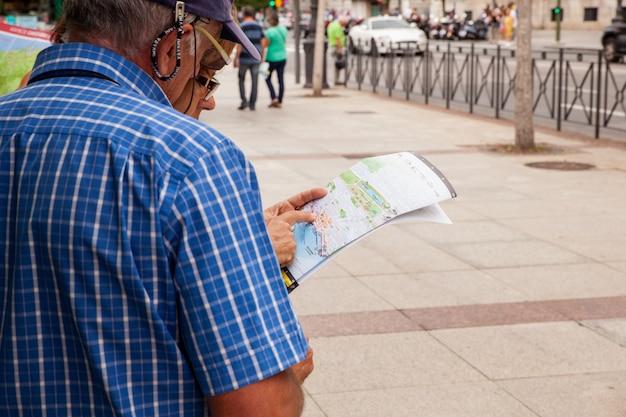 Manntourist mit karte auf der straße