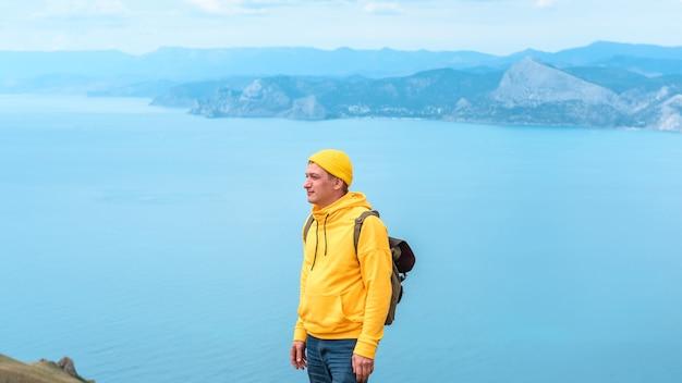 Manntourist mit rucksack auf dem meer. sommerreisekonzept