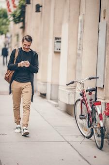 Manntourist mit rucksack in europa-straße. kaukasischer junge, der mit karte der europäischen stadt schaut.