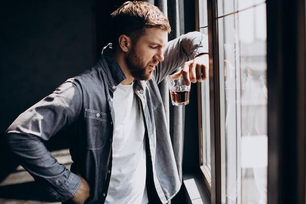 Manntrinker deprimiert mit einer flasche whisky