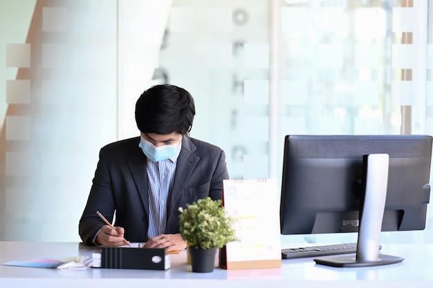 Mannunternehmer, der medizinische maske trägt, die vor computer sitzt und nützliche informationen in notizbuch im büro schreibt.