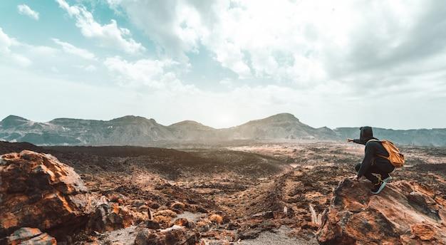 Mannwanderer auf der spitze des berges, der auf den sonnenuntergangspanoramablick zeigt. erfolgreiches, motivierendes und inspirierendes konzept