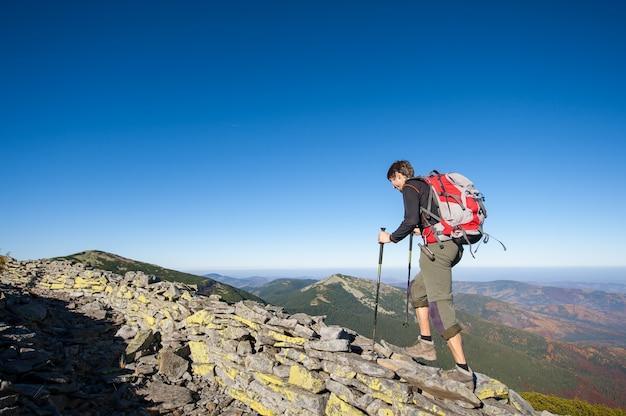 Mannwanderer, der auf den felsigen kamm des berges geht