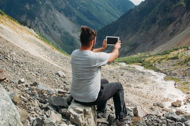 Mannwanderer, der foto mit seiner tablette macht