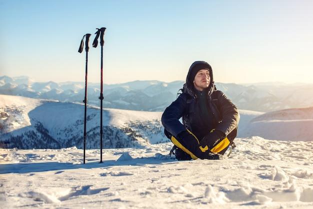 Mannwanderertouristen, die nach einem harten aufstieg allein meditierend sitzen