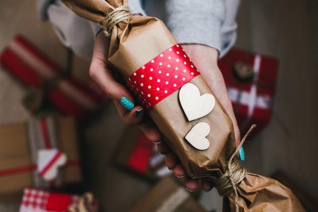 Manos con un paquete marrón con un corazón