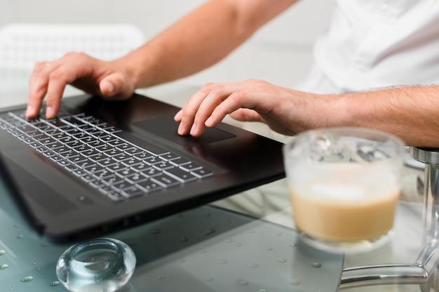 Mans hände drücken die tasten des laptops