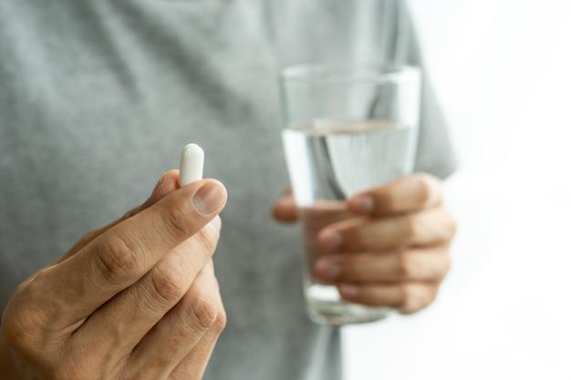 Mans hand, die pille oder medizin hält und ein glas wasser aufhebt männer, die medikamente einnehmen