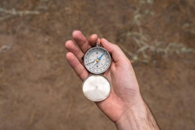 Mans hand hält einen kompass im wald