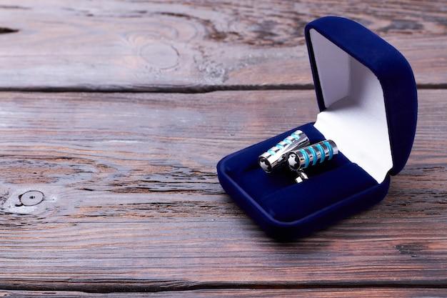 Manschettenknöpfe in samtblauer box. etui mit manschettenknöpfen auf holz. formales accessoire im stilvollen look.