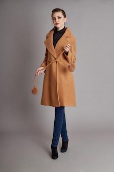 Mantel des modemädchens im frühjahr auf grauem hintergrund