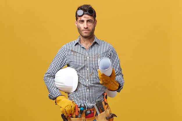 Manuelle arbeit, wartung, berufskonzept. schmutziger mechaniker, der eine schutzbrille auf dem kopf, schutzhandschuhe, hemd hält, das gerolltes papier und helm hält. fleißiger junger baumeister mit instrumenten