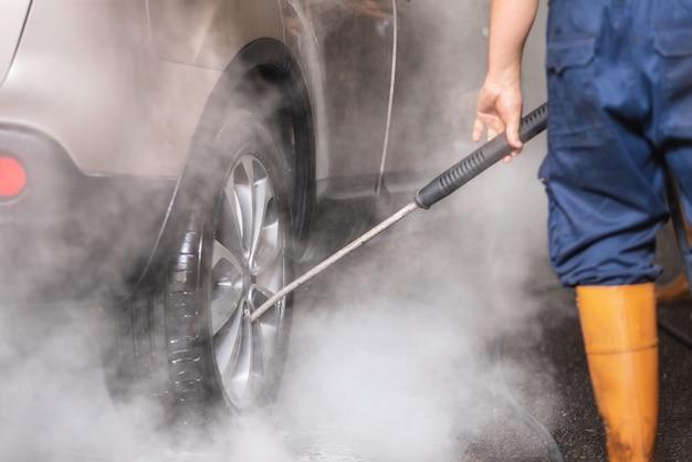 Manuelle autowäsche mit druckwasser in der autowäsche draußen.