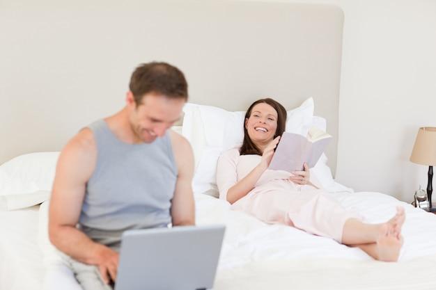 Manworking auf seinem laptop, während seine frau ein buch auf dem bett liest