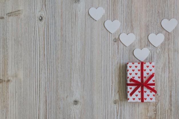 Marco gris con dos regalos y un corazón blanco