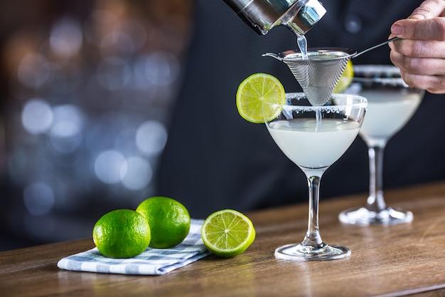 Margarita. margatita alkoholisches cocktailgetränk auf der bartheke im pub oder restaurant. barkeeper bereitet einen cocktail zu.