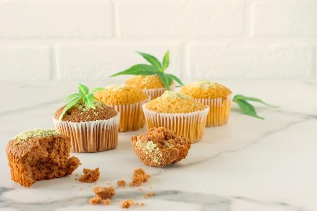 Marihuana-cupcake-muffins und cannabisblätter auf einem weißen marmortisch. hausgemacht.