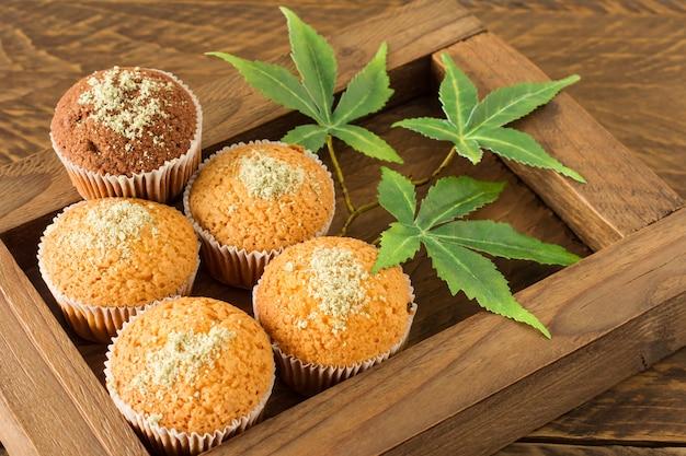 Marihuana-cupcake-muffins und cannabisblätter in einer holzkiste. hausgemacht. süßes essen mit hanf.