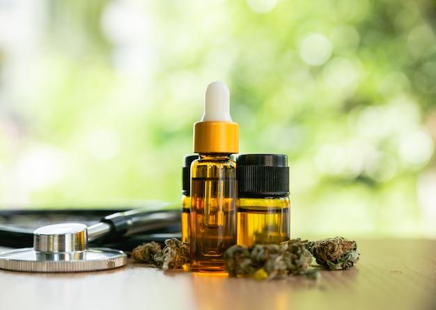 Marihuanaanlage mit den knospen und ätherischem öl auf einem holztisch, marihuana-kräuterkrebsbehandlungskonzept.