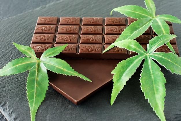 Marihuanablätter und dunkle schokolade auf schwarzem hintergrund.