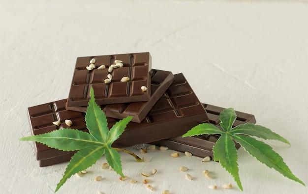 Marihuanablätter und dunkle schokolade auf weiß