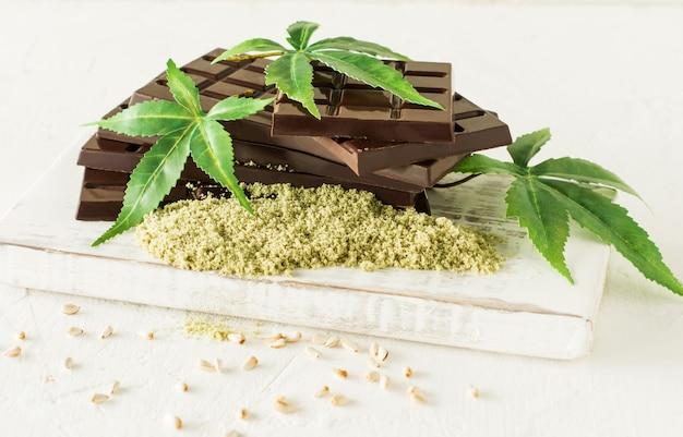 Marihuanablätter und dunkle schokolade auf weißem hintergrund.