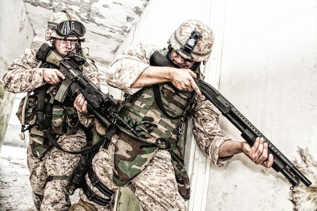 Marine-angriffsteam, mitglieder des anti-terror-trupps, kommandokämpfer in körperpanzerung, bewaffnet mit dienstgewehren, die durch den korridor zur geschlossenen tür pirschen, räume in einem verlassenen stadtgebäude räumen