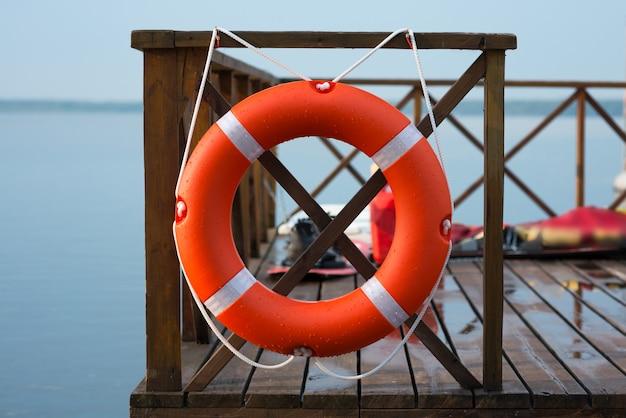 Marine rettungsring auf zaun auf wasseroberfläche