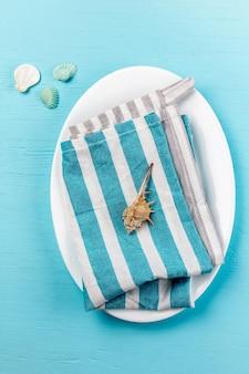 Marinegedeck mit weißen platten- und seedekorationsoberteilen auf hölzernem blau