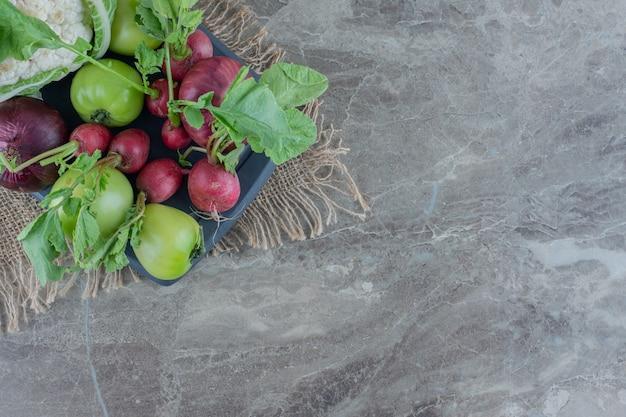 Marineplatte mit roten zwiebeln, blumenkohl, grüner tomate, rüben und rübenblättern auf marmor.