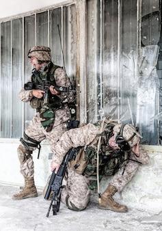 Marines angriffsteam kämpft unter stadtbedingungen und bricht unter intensivem feindlichem feuer. armee-sergeant schreit befehle, während der schütze in die hocke geht, nachdem eine kugel in der nähe seines kopfes getroffen und glas zerbrochen hat