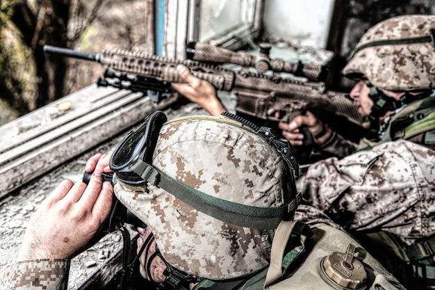 Marines scharfschützenteam, bewaffnet mit großkalibrigem, anti-materiellem scharfschützengewehr, das sich in einem zerstörten stadtgebäude versteckt, feindliche ziele aus der entfernung aus dem unterstand abschießt und im hinterhalt sitzt militärisches feuergefecht in der stadt