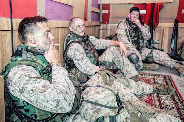 Marinesoldaten der vereinigten staaten in tarnuniform und munition, die auf dem boden eines kampfaußenpostens oder einer temporären basis auf mission sitzen, in entspannter atmosphäre sprechen und sich nach einem harten tag im militärdienst ausruhen