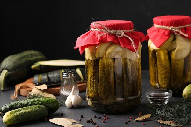 Marinierte gurken und zucchini in gläsern auf dunkel