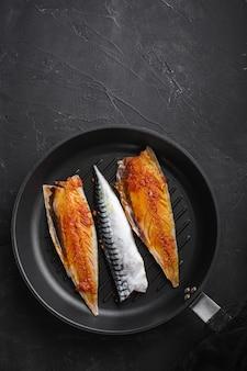 Marinierte makrele auf grillpfanne auf schwarzem hintergrund