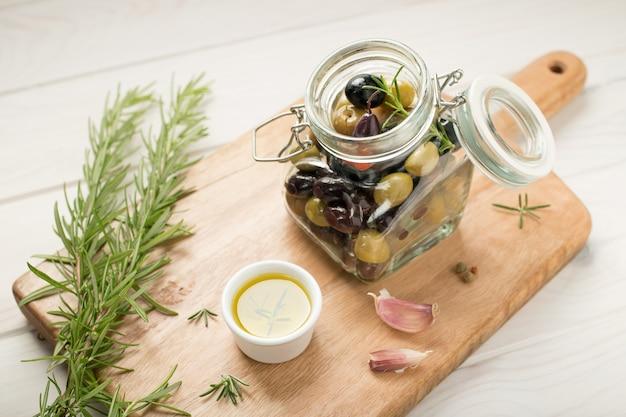 Marinierte oliven im glas auf holztisch