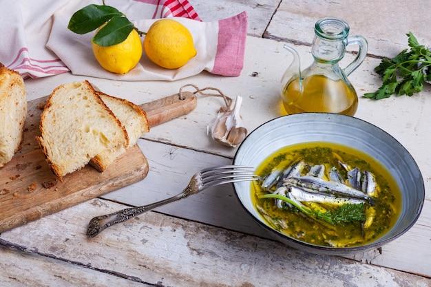 Marinierte sardellen in zitronensaft mit olivenöl, knoblauch und petersilie. traditionelles mediterranes sommeressen