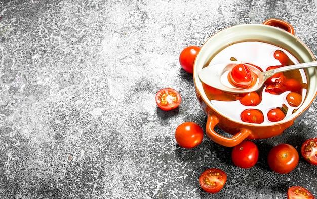 Marinierte tomaten in einer schüssel auf einem rustikalen tisch.