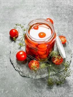 Marinierte tomaten mit kräutern. auf einem steinernen hintergrund.